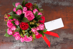 Beautiful bouquet of pink roses with gift tag and red ribbon in. A concept of love, romance, anniversary, Valentines day or wedding Stock Photos