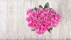 Beautiful bouquet of pink roses in heart shape on wooden backgro Stock Photo