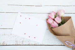 Beautiful bouquet of pink tulips next to a white envelope and pink sugar hearts Stock Photo