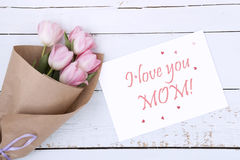 Beautiful bouquet of pink tulips next to a white envelope and pink sugar hearts Stock Images