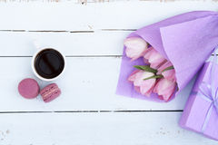 Beautiful bouquet of pink tulips in violet paper, gift, cup of coffee and two pink macaroons Royalty Free Stock Image