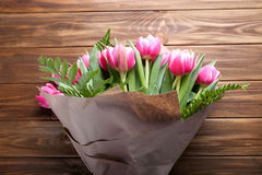 Beautiful bouquet of pink tulips wrapped in paper on wooden back. Beautiful pink tulips wrapped in paper on wooden background Royalty Free Stock Photography