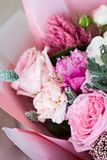 Beautiful bouquet in pink wrapping paper. Roses and other delicate beautiful flowers stock photography