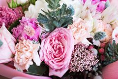 Beautiful bouquet in pink wrapping paper. Roses and other delicate beautiful flowers stock image