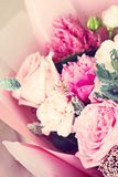 Beautiful bouquet in pink wrapping paper. Roses and other delicate beautiful flowers stock photo