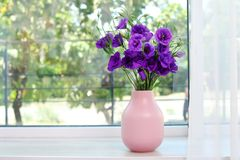 Beautiful bouquet of purple eustoma flowers. In vase near window with space for text royalty free stock photography