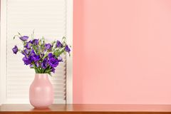 Beautiful bouquet of purple eustoma flowers in vase near color wall. With space for text stock image
