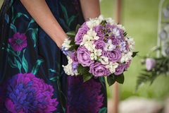 Beautiful bouquet of purple roses in their hands Royalty Free Stock Photo