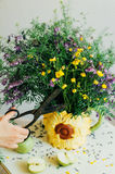 Beautiful bouquet of purple and yellow wildflowers in the room light on a white table. Stock Image