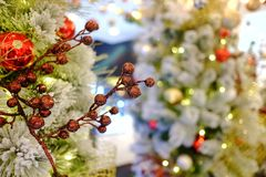 A beautiful bouquet of red flower ornament hanging from a white Christmas tree royalty free stock images