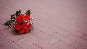 Beautiful bouquet of red rose lying on road. Wedding Royalty Free Stock Image