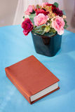 Beautiful bouquet of rose flower in black vase on table with old vintage notebook on Linen blue background Stock Photo