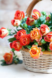 Beautiful bouquet of roses in basket on wooden table, selective Royalty Free Stock Photo