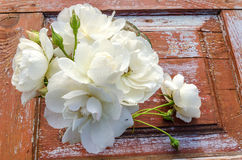Beautiful bouquet of roses with drops on old wooden table. Overhead view Royalty Free Stock Images