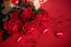 Beautiful bouquet of roses with a gift boxes on a red background stock images