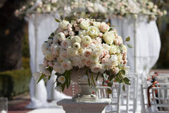 Beautiful bouquet of roses in a vase on a background of a wedding arch. Beautiful set up for the wedding ceremony. Stock Photography