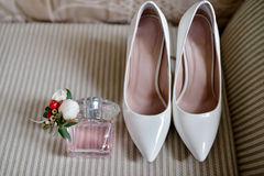 Beautiful bouquet, shoes and perfume bottle for bride and groom. Beauty of wedding accessories indoors. Close-up bridal bunch of florets and perfumery. Female Stock Photography