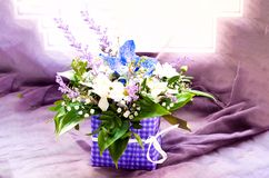 Beautiful bouquet of spring flowers on purple texture on window background royalty free stock images