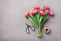 Beautiful bouquet of spring pink tulips flowers on stone table top view in flat lay style. royalty free stock image