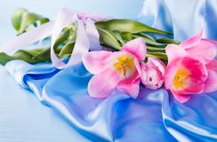 Beautiful bouquet of tender pink tulips lying on blue satin fabr Stock Photos