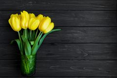Beautiful bouquet of tulips in glass vase on table. Top view, flat lay. Beautiful bouquet of yellow tulips in green vintage glass vase on dark wooden table Stock Photography