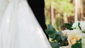 Beautiful bouquet and various delicate flowers. Lies on the background of a blurry, elegant bride and groom on a sunny warm summer day in nature. The concept of stock video