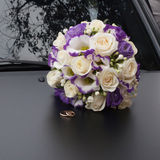 Beautiful bouquet and wedding rings on black car Royalty Free Stock Image