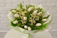Beautiful bouquet with white tulips and camomiles royalty free stock photo