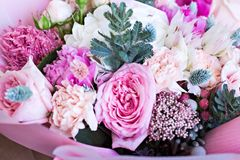 Beautiful bouquet in pink wrapping paper. Roses and other delicate beautiful flowers stock photos