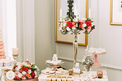 Beautiful bouquets of flowers on the table with sweets Royalty Free Stock Image