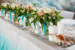 Beautiful bouquets of roses and decorations on table Stock Photos