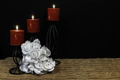Beautiful bouquie of white roses, red candles perched on black candle holders on mesh place mat and wooden table with card and dar stock image