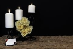 Beautiful bouquie of yellow roses, white candles perched on black candle holders on mesh place mat and wooden table with card and stock photography