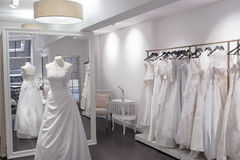 Beautiful Boutique wedding store. Wedding dress shop with mannequin, full length mirror, and selection of wedding gowns Stock Photo