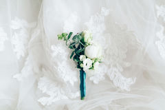 Beautiful boutonniere on white wedding dress, closeup. Beautiful boutonniere on white wedding dress as background. Closeup stock photo