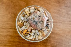 A bowl of rocks sits as a center piece for a table decoration in a person`s home. royalty free stock photos