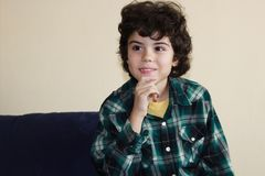 Beautiful boy. Studio portrait of a boy in colorful shirt sitting on a sofa Royalty Free Stock Photography