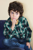 Beautiful boy. Studio portrait of a boy in colorful shirt sitting on a sofa Stock Photography