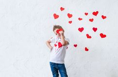 Beautiful boy on the background of hearts. Cute boy are preparing for Valentine`s Day royalty free stock image