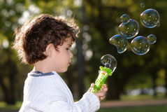 Beautiful boy blowing soap bubbles Stock Photos