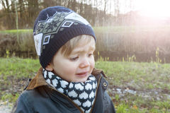 Beautiful boy crying outdoors. Portrait of a crying toddler at sunset Stock Photos