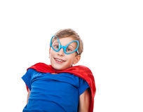 Beautiful boy dressed as superman sitting and smiling. Beautiful happy child wearing funny glasses dressed as superhero sitting and smiling Stock Images