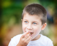 Beautiful boy eating. A healthy food outdoor Stock Image