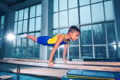 Beautiful boy is engaged in sports gymnastics on a parallel bars. The little boy is engaged in sports gymnastics on a parallel bars at gym. The performance royalty free stock photo