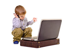 Beautiful boy gesticulating hands speaks on the phone. Looking at laptop Royalty Free Stock Photo