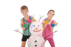 Beautiful boy and girl with hands in paint near color snowman with colored horns and hands Stock Photo