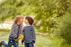 Beautiful boy and girl in a park, boy giving flowers to the girl. Friendship concept Royalty Free Stock Image