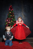 Beautiful boy and girl in the photo studio on a black background. On a black background in a Christmas tree in suits on the red carpet royalty free stock photography