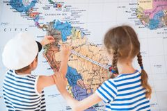 Beautiful boy and a girl in sailor striped shirts measure distance on world map with measuring tape. Beautiful kid and a girl in sailor striped shirts measure royalty free stock photos