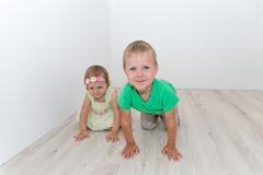 Beautiful boy and girl sitting on the floor Stock Images